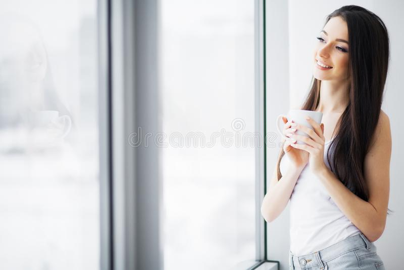 Mujer hermosa que coloca ventanas cercanas Ma?ana hermosa foto de archivo