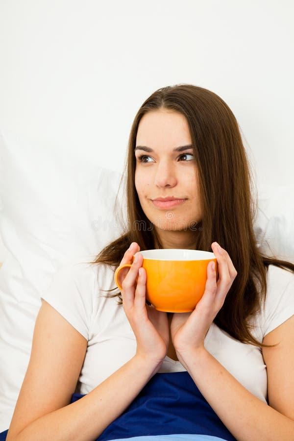 Mujer hermosa que come café en cama fotografía de archivo