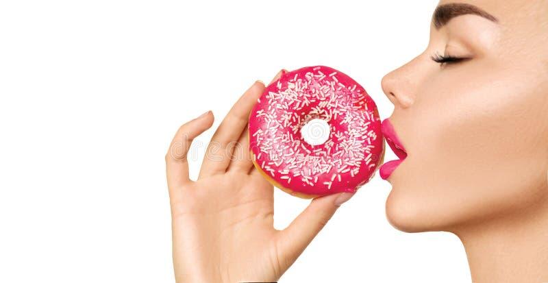 Mujer hermosa que come el buñuelo rosado fotos de archivo