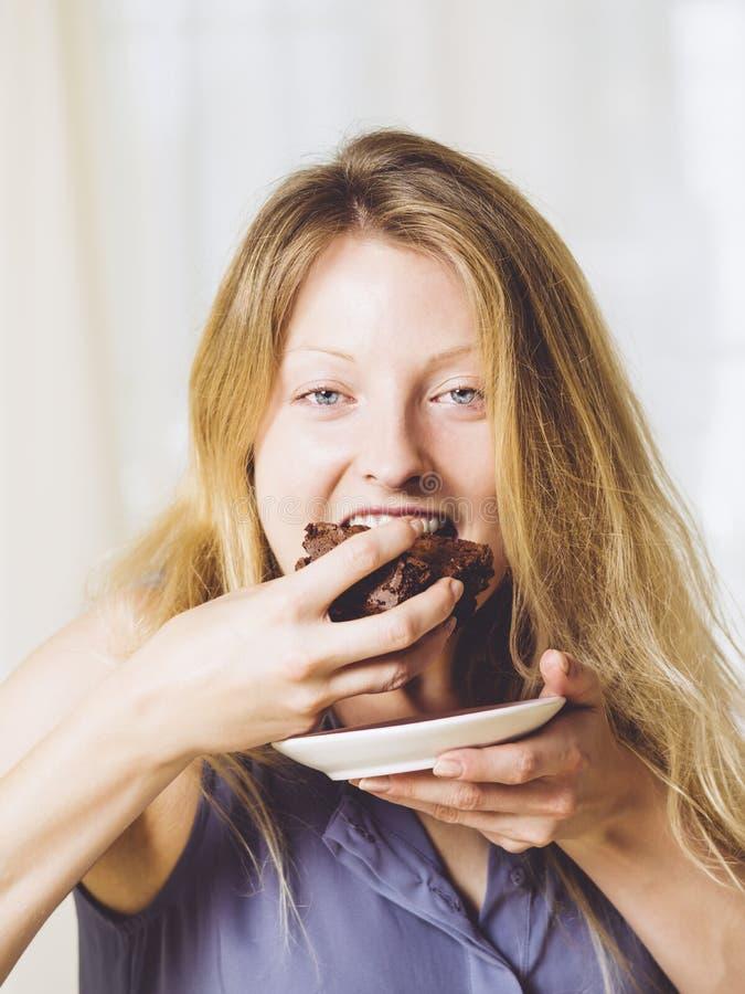 Mujer hermosa que come un brownie imagen de archivo libre de regalías