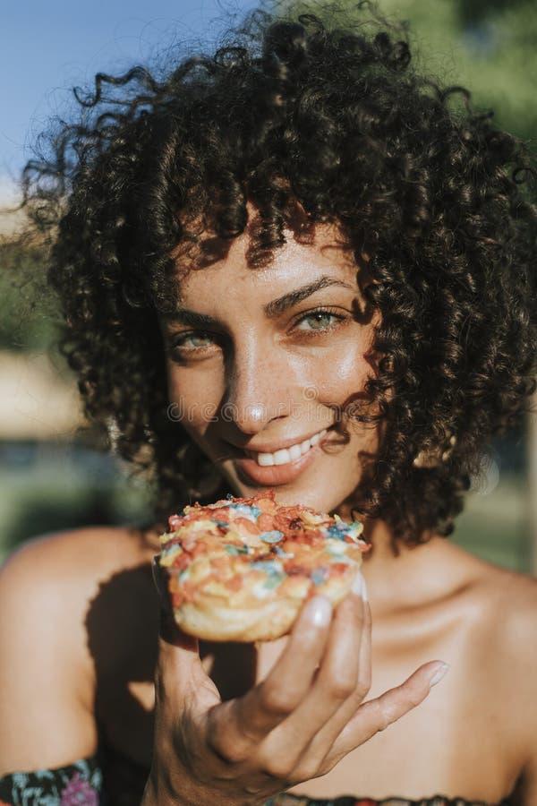 Mujer hermosa que come un buñuelo fotografía de archivo libre de regalías