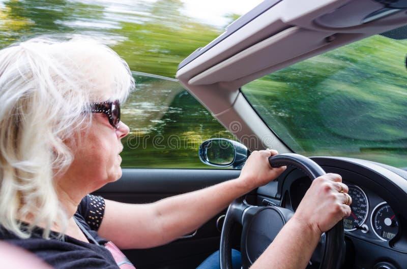 Mujer hermosa que conduce el coche convertible fotografía de archivo