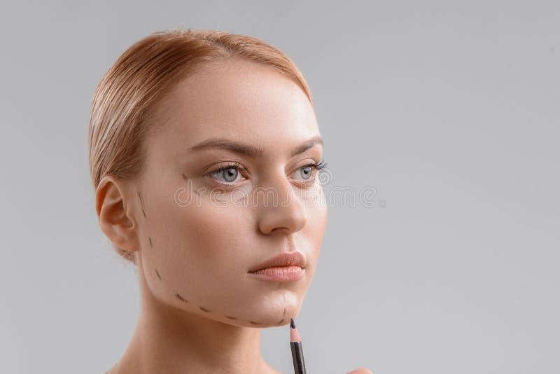 Mujer hermosa que consigue líneas de perforación en su cara fotografía de archivo