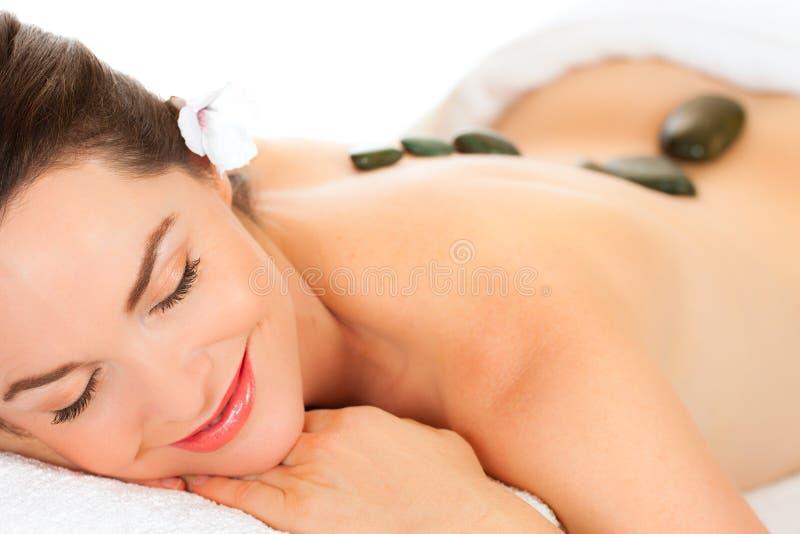 Mujer hermosa que consigue masaje de piedra caliente imagen de archivo libre de regalías