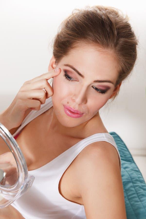 Mujer hermosa que controla su maquillaje imagen de archivo libre de regalías