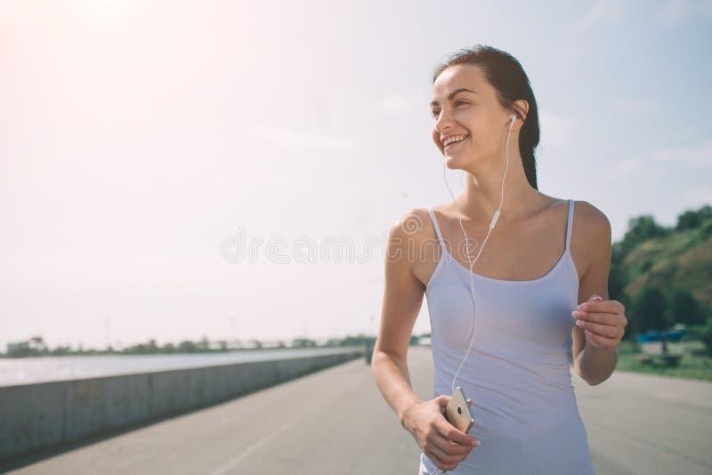 Mujer hermosa que corre durante puesta del sol Modelo joven de la aptitud cerca de la playa Vestido en ropa de deportes fotografía de archivo