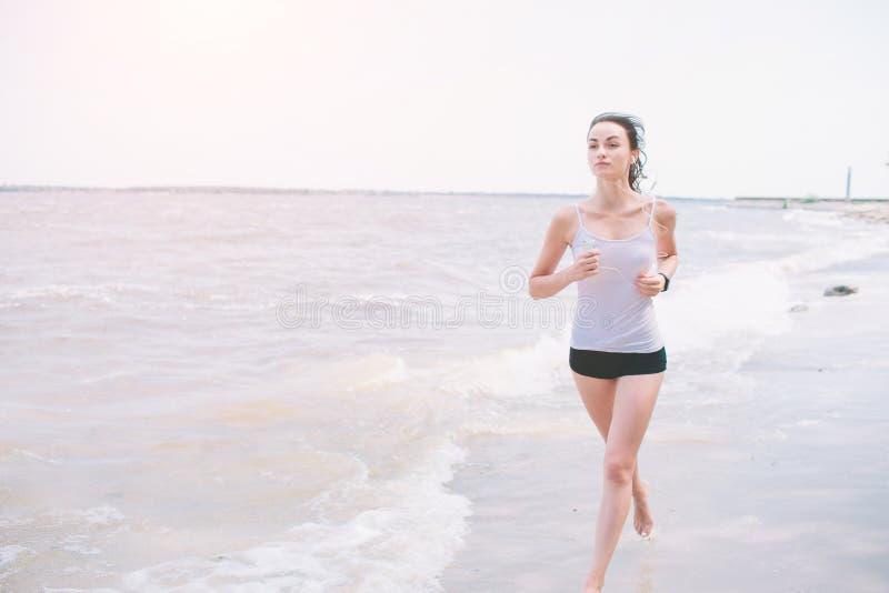 Mujer hermosa que corre durante puesta del sol Modelo joven de la aptitud cerca de la playa Vestido en ropa de deportes fotos de archivo