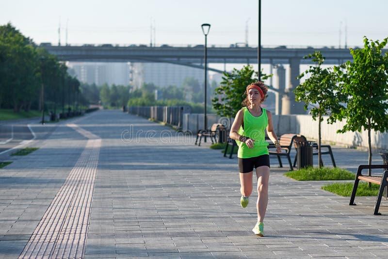 Mujer hermosa que corre sobre el puente durante puesta del sol imagen de archivo libre de regalías