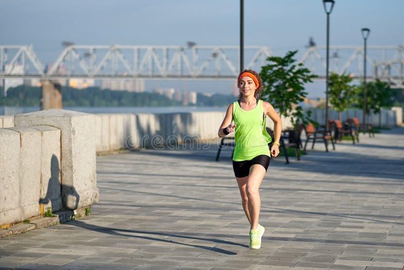 Mujer hermosa que corre sobre el puente durante puesta del sol foto de archivo