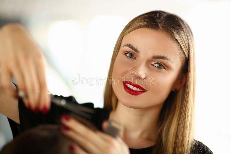 Mujer hermosa que corta el pelo masculino en salón de belleza imagenes de archivo