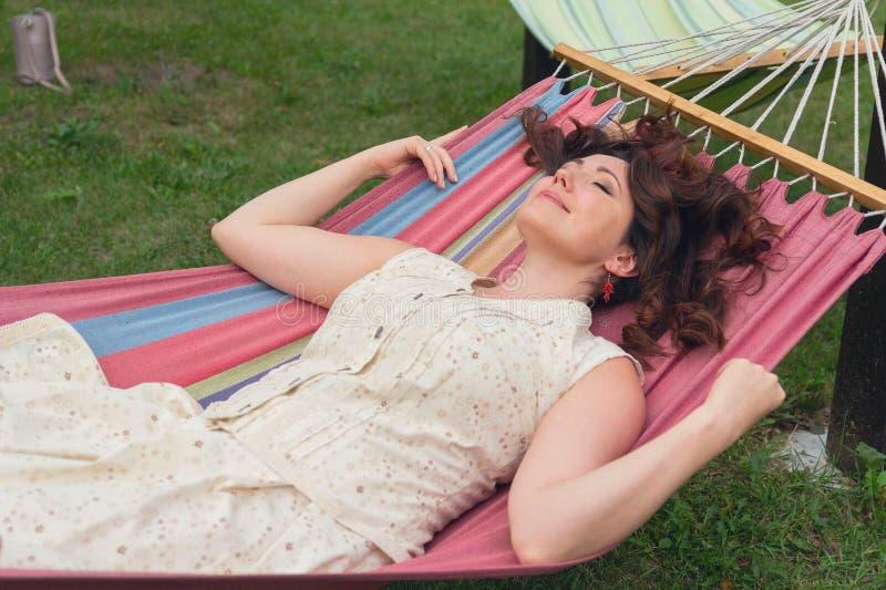 Mujer hermosa que descansa en una hamaca fotos de archivo