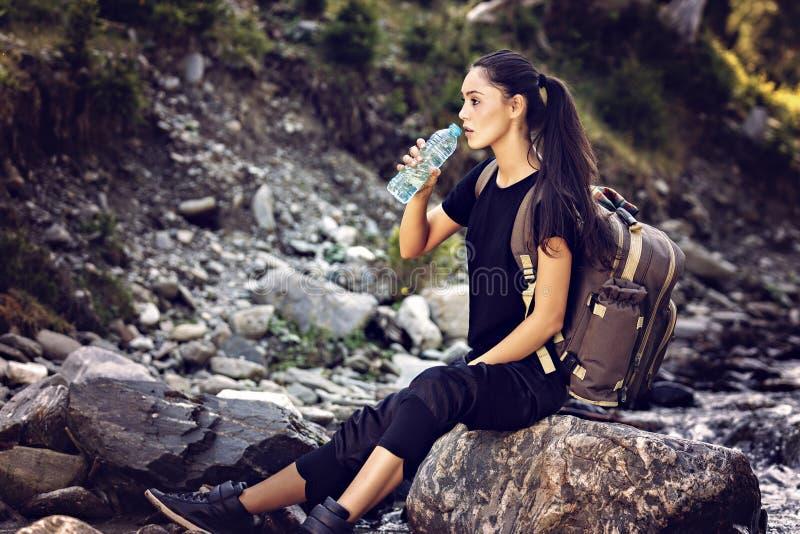 Mujer hermosa que descansa sobre una roca en el río y el wate de consumición imagenes de archivo
