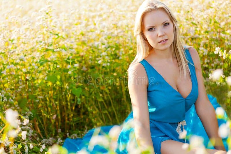 Mujer hermosa que desgasta la alineada azul en un campo imagen de archivo