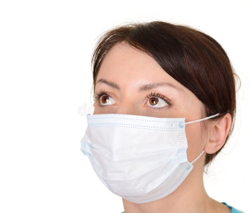 Mujer hermosa que desgasta la máscara quirúrgica aislada en el fondo blanco imágenes de archivo libres de regalías