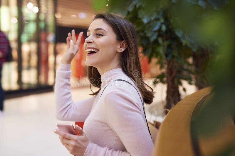 Mujer hermosa que dice hola y que agita su mano fotos de archivo libres de regalías