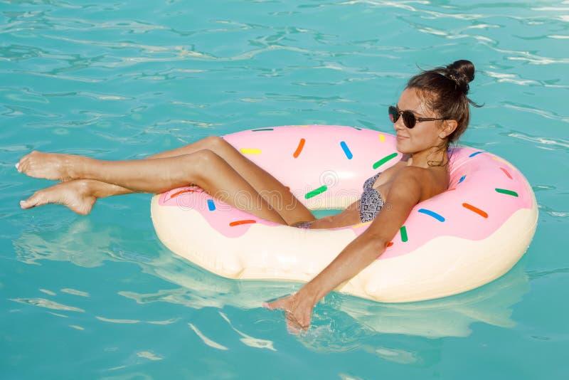 Mujer hermosa que disfruta de día de verano caliente en el poolside fotos de archivo