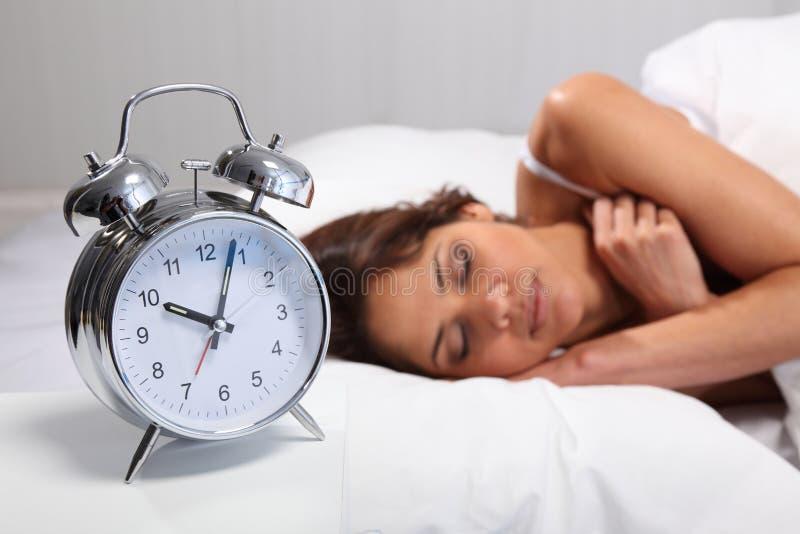Mujer hermosa que duerme con el reloj de alarma próximo imagen de archivo