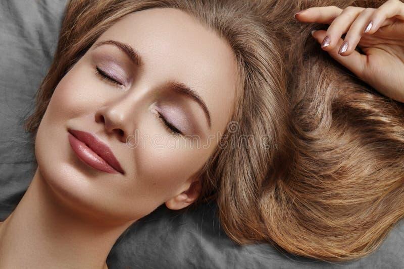 Mujer hermosa que duerme mientras que miente en cama con comodidad Sueños dulces Modelo atractivo con el pelo rizado que se relaj imagen de archivo
