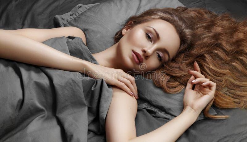 Mujer hermosa que duerme mientras que miente en cama con comodidad Sueños dulces modelo que se relaja en las hojas grises fotografía de archivo libre de regalías