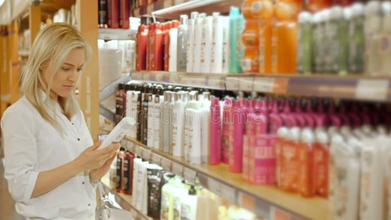 Mujer hermosa que elige productos del cuidado del cuerpo en supermercado imagen de archivo