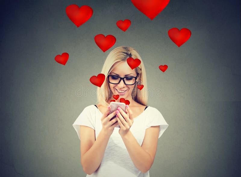 Mujer hermosa que envía el mensaje de texto del amor en el teléfono móvil con los corazones rojos que vuelan lejos de la pantalla fotos de archivo