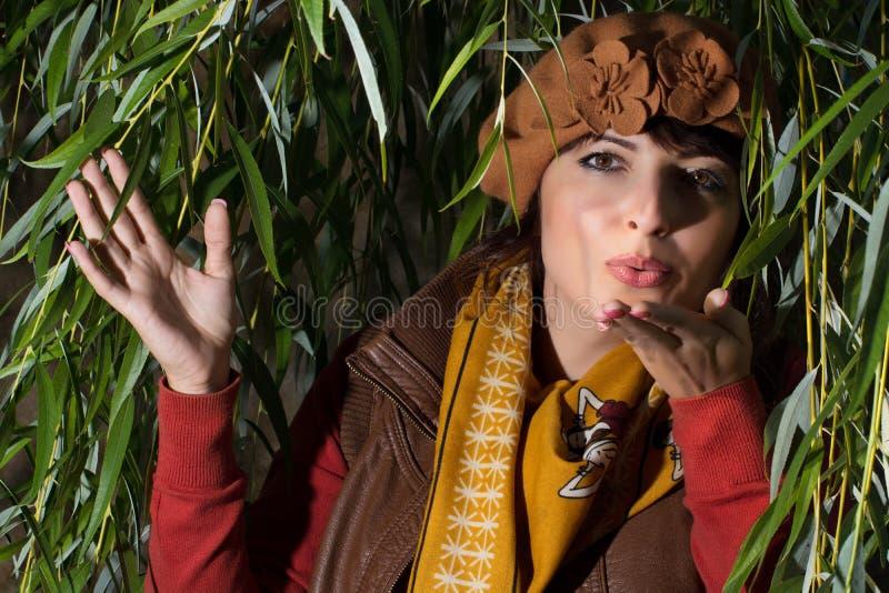 Mujer hermosa que envía un beso debajo del sauce fotografía de archivo libre de regalías