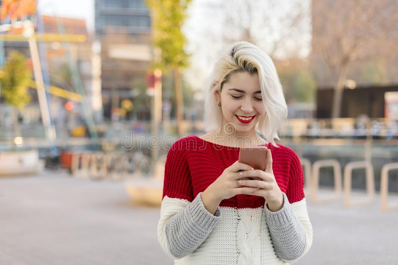 Mujer hermosa que escribe un mensaje en su teléfono imagen de archivo