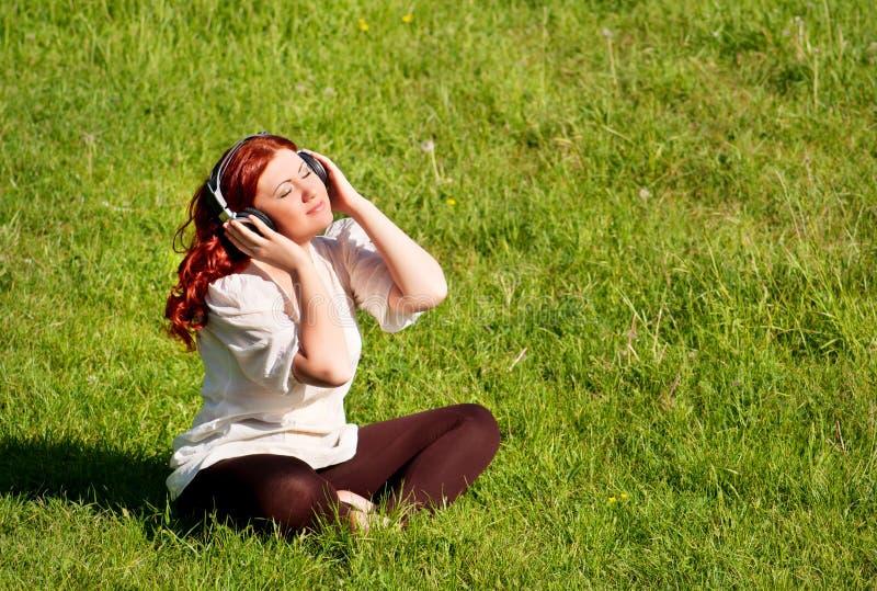 Mujer hermosa que escucha la música con los auriculares imagen de archivo