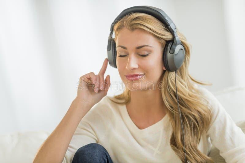 Mujer hermosa que escucha la música a través de los auriculares fotografía de archivo libre de regalías