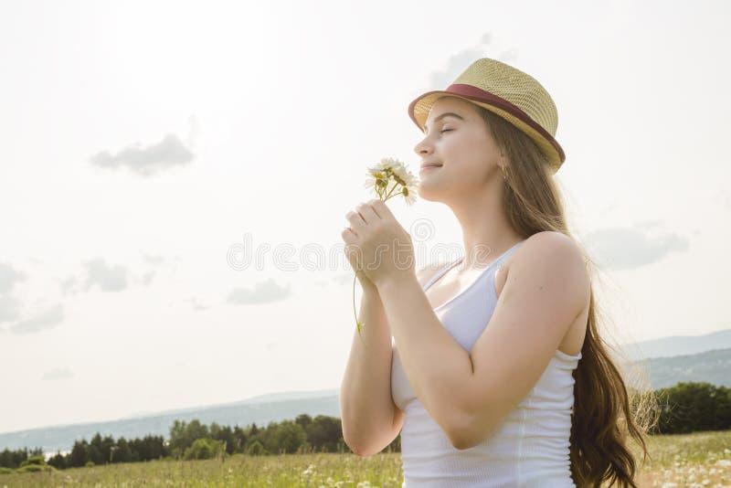 Mujer hermosa que goza de la margarita en un campo imagenes de archivo