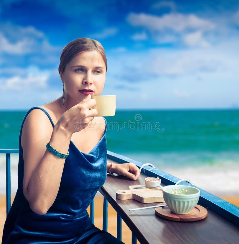 Mujer hermosa que goza de t? en terraza del caf? en la playa fotografía de archivo