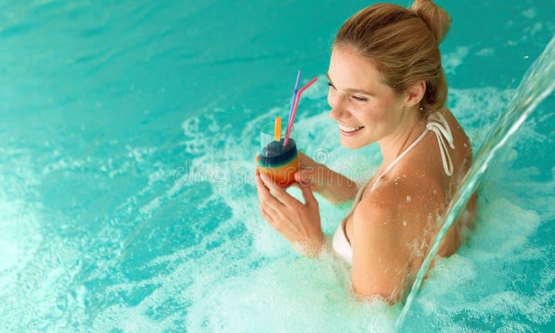 Mujer hermosa que goza del jet del agua en centro turístico de la salud fotografía de archivo libre de regalías