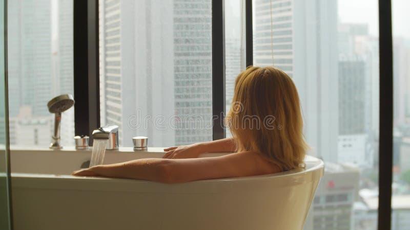 Mujer hermosa que goza relajando el baño en cuarto de baño de lujo con una ventana Concepto del cuidado de la forma de vida y de  imagen de archivo