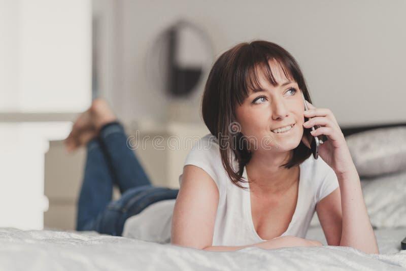 Mujer hermosa que habla en smartphone en su dormitorio imágenes de archivo libres de regalías