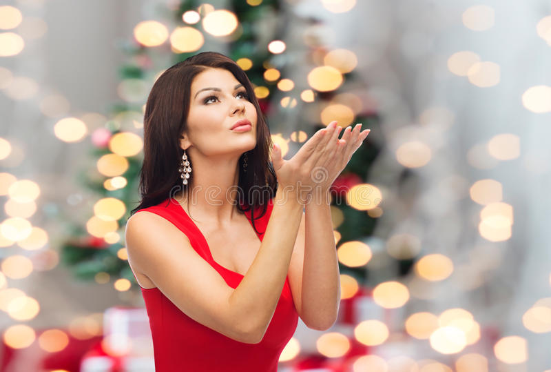 Mujer hermosa que hace deseo de la Navidad sobre luces foto de archivo
