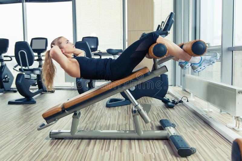 Mujer hermosa que hace ejercicio de la aptitud de la prensa en el gimnasio del deporte imagen de archivo