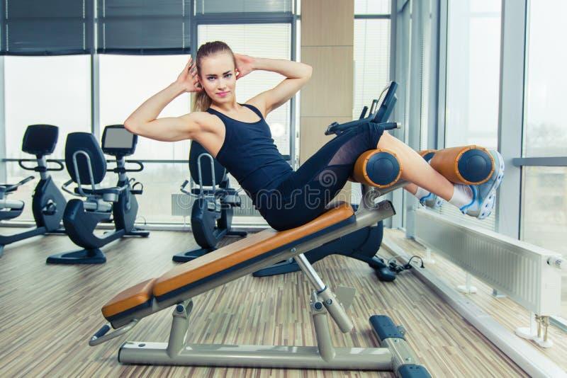 Mujer hermosa que hace ejercicio de la aptitud de la prensa en el gimnasio del deporte imagenes de archivo