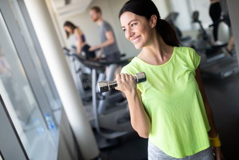 Mujer hermosa que hace ejercicios con pesa de gimnasia en gimnasio La muchacha está gozando con su proceso de entrenamiento fotos de archivo