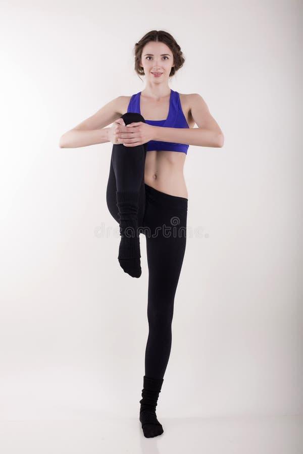 Mujer hermosa que hace estirar en el estudio blanco foto de archivo libre de regalías