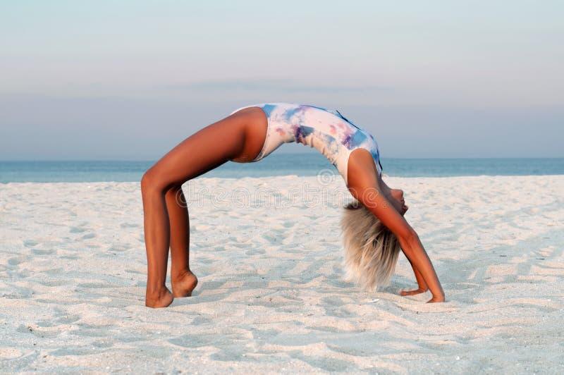Mujer hermosa que hace la yoga, actitud de Urdhva Dhanurasana en la playa imagenes de archivo