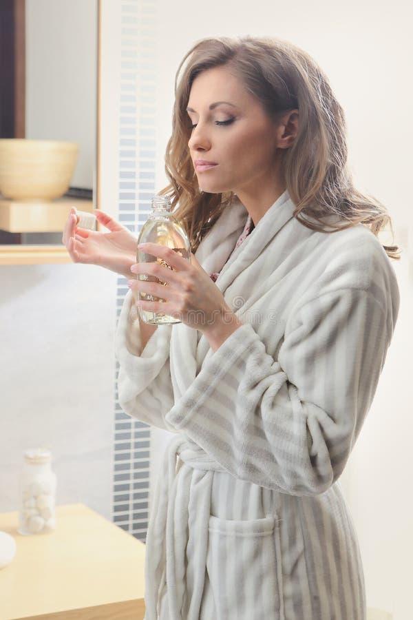 Mujer que huele su perfume fotos de archivo libres de regalías