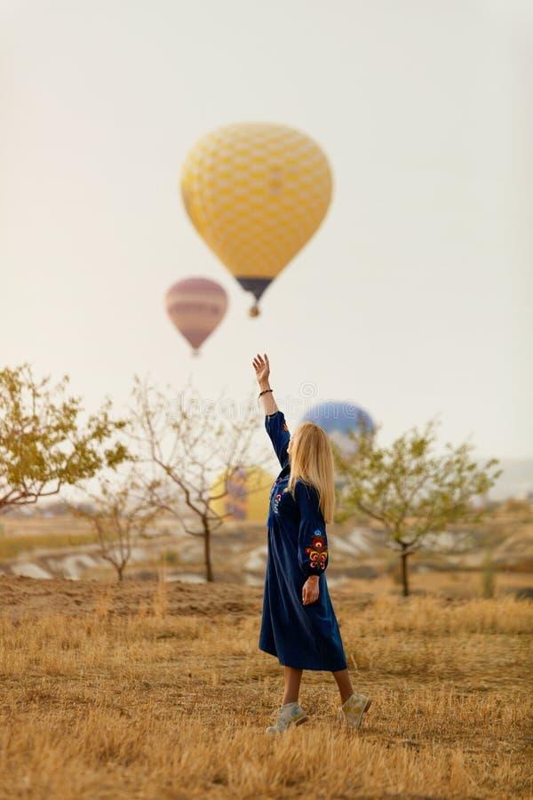 Mujer hermosa que intenta alcanzar el globo del aire caliente en cielo con la mano foto de archivo