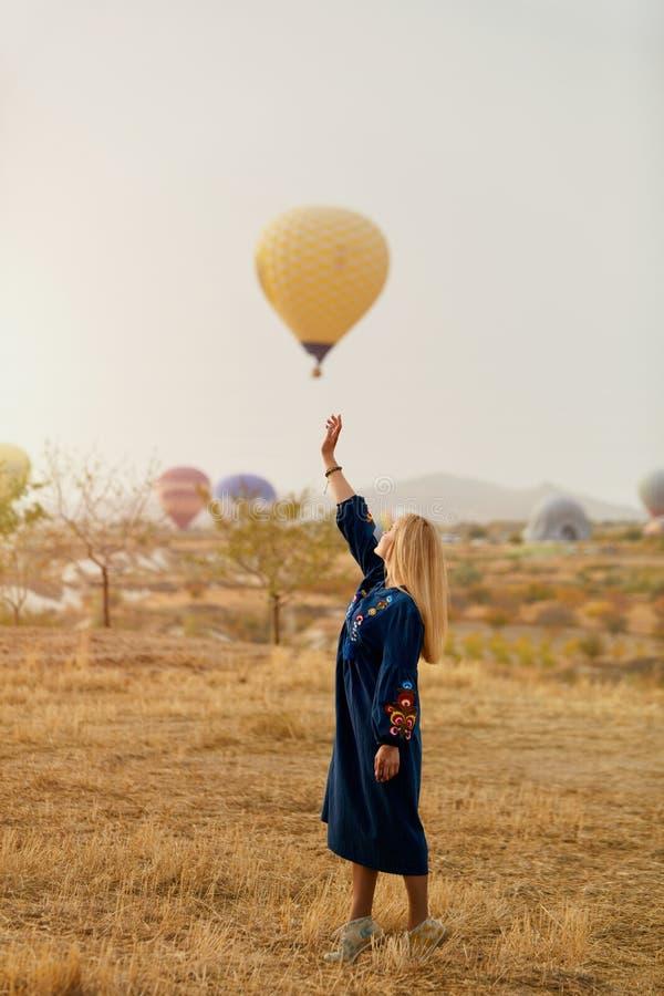 Mujer hermosa que intenta alcanzar el globo del aire caliente en cielo con la mano imagen de archivo