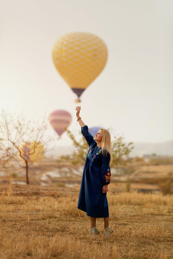 Mujer hermosa que intenta alcanzar el globo del aire caliente en cielo con la mano fotos de archivo