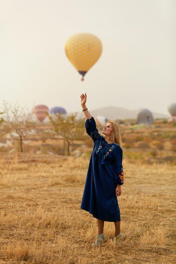 Mujer hermosa que intenta alcanzar el globo del aire caliente en cielo con la mano fotografía de archivo libre de regalías