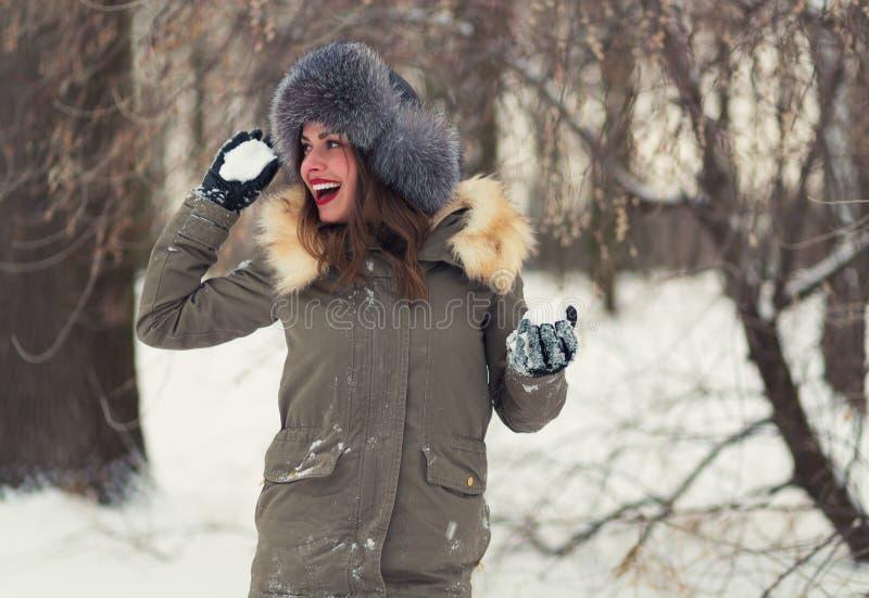 Mujer hermosa que juega bolas de nieve foto de archivo