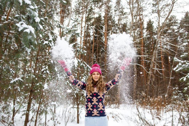 Mujer hermosa que juega la bola de nieve en el bosque del invierno fotografía de archivo