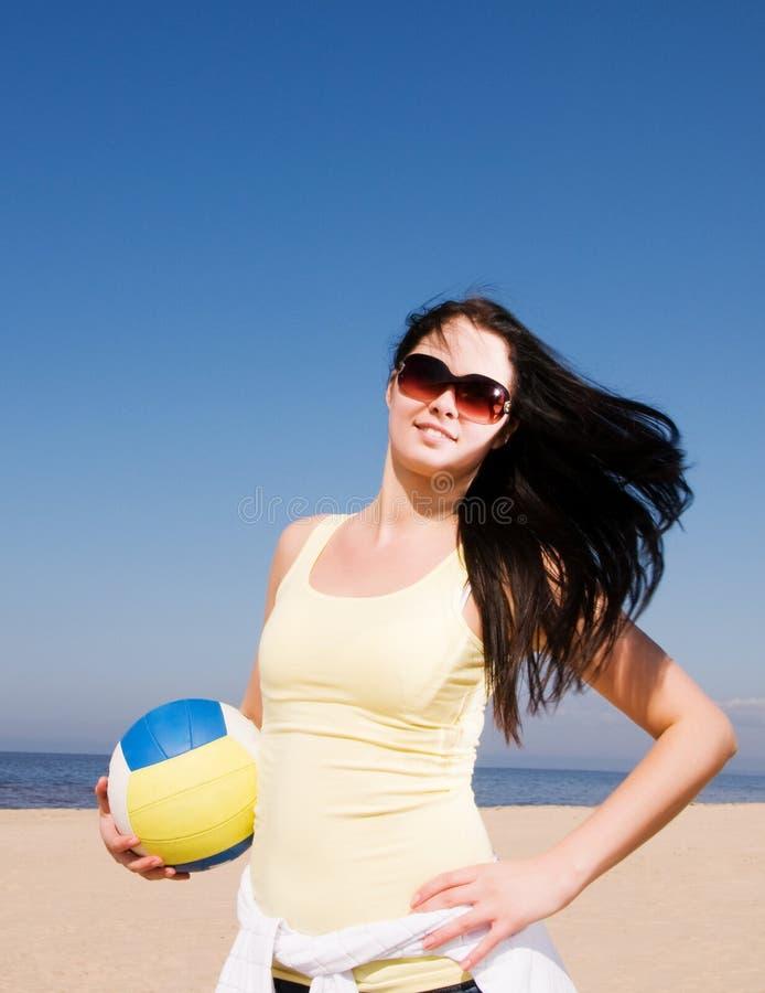 Mujer hermosa que juega a voleibol en la playa foto de archivo libre de regalías