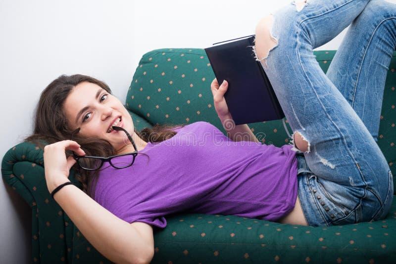 Mujer hermosa que lee un libro que miente comfortablemente fotografía de archivo libre de regalías