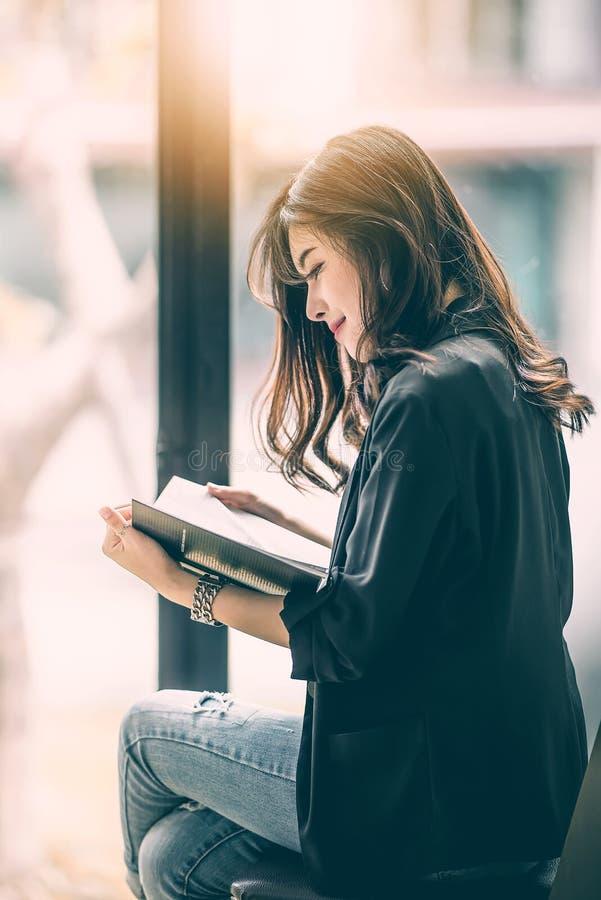 Mujer hermosa que lee un libro por la ventana imagen de archivo